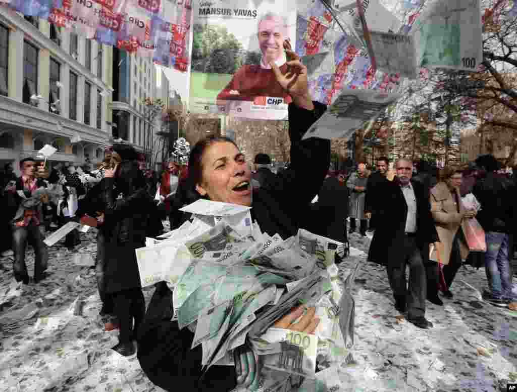 Members of the main opposition Republican People's Party throw fake Euro bills into the air during an anti-government protest denouncing a corruption scandal that has shaken Prime Minister Recep Tayyip Erdogan's government, in Ankara, Turkey.