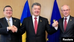 Ukraine's President Petro Poroshenko poses with European Commission President Jose Manuel Barroso (L) and European Council President Herman Van Rompuy (R) at the EU Council in Brussels, June 27, 2014.