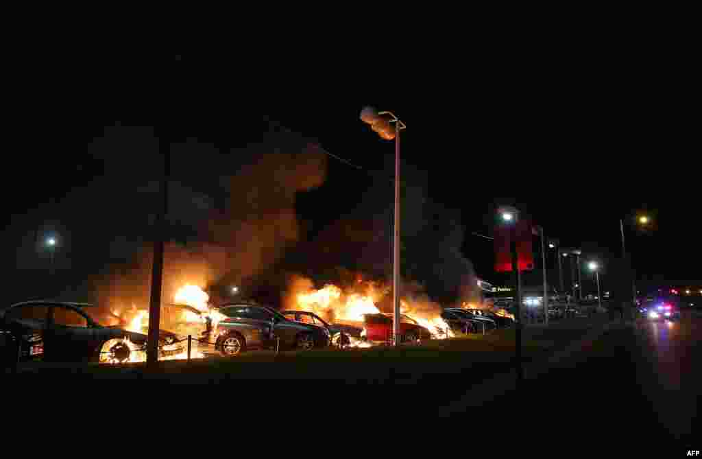A row of cars burn at a used car lot during a demonstration in Ferguson, Missouri. Ferguson has been struggling to return to normal after Micahel Brown, an 18-year-old black man, was killed by Darren Wilson, a white police officer, on Aug. 9. A grand jury declined to indict officer Wilson.