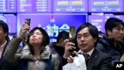 30일 일본 도쿄 증권거래소에서 방문객들이 증시현황판을 보고 있다.