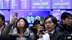 Para pengunjung mengabadikan angka-angka harga saham yang tertera pada layar di lantai bursa saham Tokyo, Minggu (30/12).Bursa Jepang ditutup lebih tinggi 57 persen, kinerja tahunan terbaik bursa itu sejak 1972.