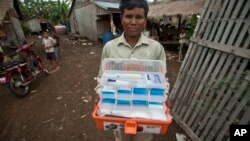 This Aug. 29, 2009 photo shows village malaria worker Phoun Sokha, 47, showing his malaria medicine kit at O'treng village on the outskirts of Pailin, Cambodia.