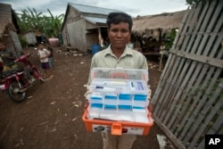 FILE - A village malaria worker shows his malaria medicine kit at O'treng village on the outskirts of Pailin, Cambodia, Aug. 29, 2009.