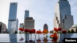 罹難者親屬在世貿中心雙子樓遺址現在是兩個方形紀念水池,插上鮮花。