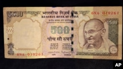 This photo illustration shows a 500 rupee Indian currency note.