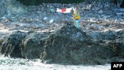 Một nhà hoạt động Nhật Bản phất cờ sau khi đặt chân trên nhóm đảo gọi là Senkaku mà Trung Quốc gọi là Điếu Ngư, ngày 19/8/2012