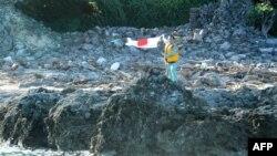 Một nhà hoạt động Nhật Bản vẫy cờ Nhật khi đặt chận lên một trong những đảo trong dãy đảo Senkaku đang trong vòng tranh chấp mà Trung Quốc gọi là Điếu Ngư