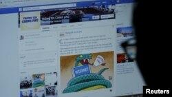 """Một người dùng mạng Facebook ở Hà Nội đang xem trang tin Thông tin Chính phủ trong bức ảnh chụp hôm 30/12/2015. Facebook đã phải tăng cường kiểm duyệt tin """"chống phá nhà nước"""" sau khi bị Việt Nam yêu cầu, theo Reuters."""