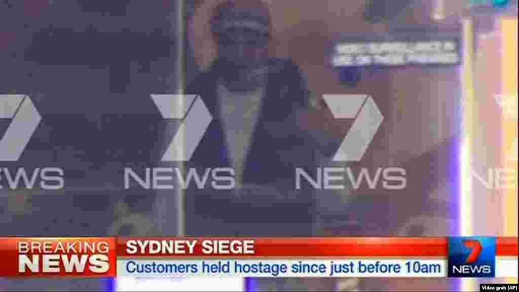 Dalam gambar yang diambil dari video ini tampak seroang pria bersenjata di dalam sebiah cafe di Sydney, Australia (15/12).