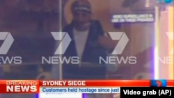 FILE - This image taken from video shows a man believed to be a gunman inside a cafe in Sydney, Australia, Dec. 15, 2014.