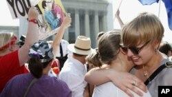 동성혼 합법화 지지자들이 26일 미국 워싱턴 DC 연방대법원 앞에서 '연방 결혼보호법' 위헌 결정에 환호하고 있다.