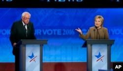 Bernie Sanders, left, listens as Hillary Clinton speaks during a Democratic presidential primary debate at Saint Anselm College in Manchester, N.H., Dec. 19, 2015.