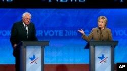 Ông Bernie Sanders, trái, nghe bà Hillary Clinton nói trong một cuộc tranh luận bầu cử sơ bộ của đảng Dân chủ tại Saint Anselm College Manchester, New Hampshire, ngày 19/12/2015.