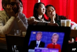 FILE - Students watch a live broadcast of the presidential debate between Democratic presidential candidate Hillary Clinton and Republican presidential candidate Donald Trump, at a cafe in Beijing.