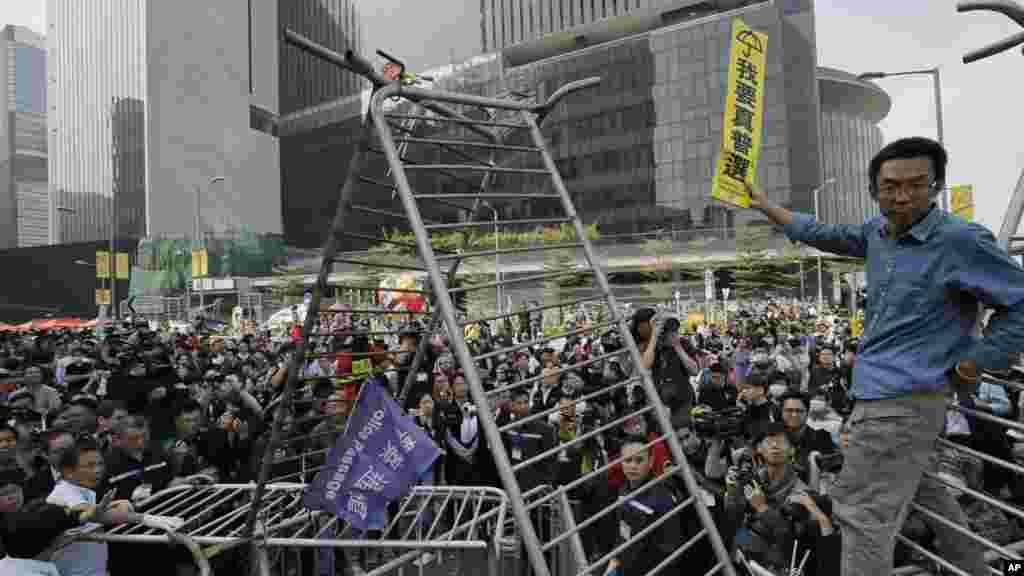 """Un manifestante prodemocracia muestra desde una barricada un rótulo que dice """"Quiero sufragio univrsal genuino""""."""