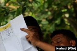 Petugas memeriksa surat suara dalam pemungutan suara. (Foto:VOA/Nurhadi.)