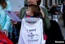 آب و ہوا کی تبدیلی سے متعلق عالمی کانفرنس کے موقع پر لندن کے مظاہرے میں ایک خاتون اپنے بچے کو اٹھائے ہوئے جس کی کرسی پر لکھا ہے کہ میرا بھی مستقبل پر حق ہے۔