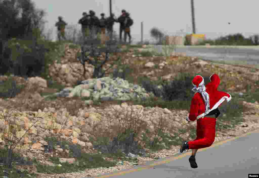 A Palestinian demonstrator dressed as Santa Claus throws stones towards Israeli troops during clashes at a protest against U.S. President Donald Trump's decision to recognize Jerusalem as the capital of Israel, near the West Bank city of Ramallah.