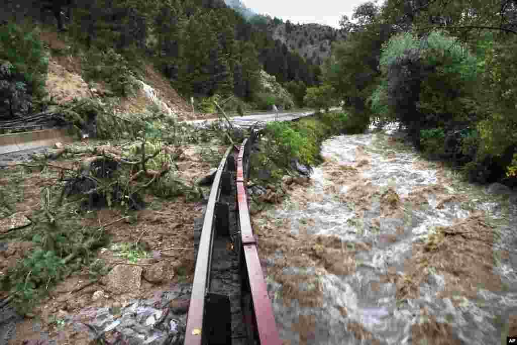 Nước lụt chảy ồ ạt trong một đường mương bên cạnh một con đường đã bị đóng vì cây cối ngả đầy. (Ảnh: AP Photo/Brennan Linsley)