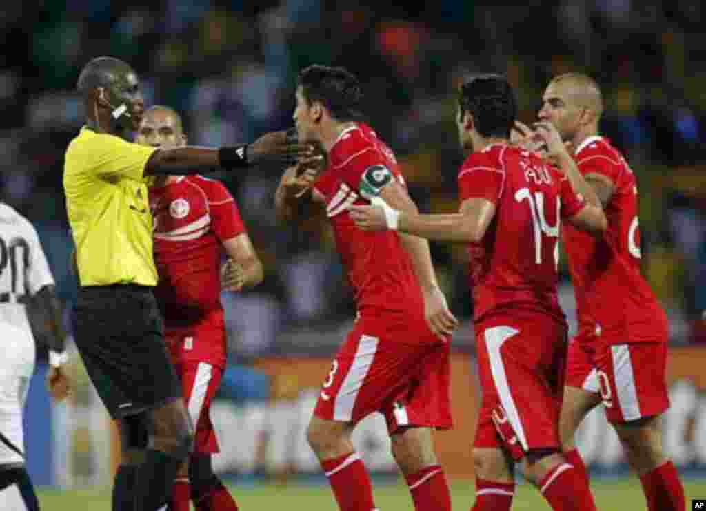 Tunisia's Karim Haggui (C) argues with referee Alioum Neant of Cameroon during their African Nations Cup quarter-final soccer match against Ghana at Franceville stadium February 5, 2012.