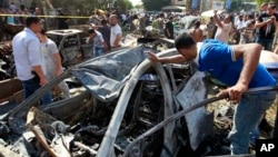 People gather outside of the Salam mosque amid charred cars and wide damage, in the northern city of Tripoli, Lebanon, Friday, Aug. 23, 2013.