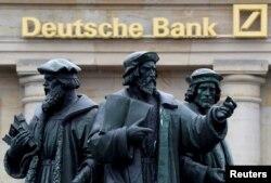 ຮູບປັ້ນຢືນຢູ່ຕໍ່ໜ້າ ສັນຍາລັກ ທະນາຄານ ຂອງເຢຍຣະມັນ ຫຼື Deutsche Bank ຢູ່ໃນນະຄອນ ຟຣັງເຟີດ໌, ເຢຍຣະມັນ, ວັນທີ 30 ກັນຍາ 2016.