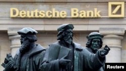 FILE - A statue stands next to the logo of Germany's Deutsche Bank in Frankfurt, Germany, Sept. 30, 2016.