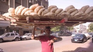 """In Egyptian Arabic, """"bread"""" and """"life"""" are the same word.  """"I feel bad for the customers because prices are going up,"""" says Sameh Soltan, who works 12 hour days selling bread in the Cairo suburbs.  He says he learned how to balance the bread on his head f"""