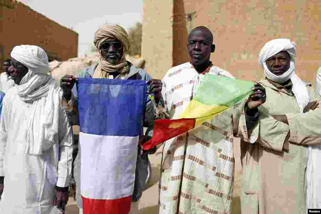People hold Malian and French flags during the reopening ceremony of Mahamane Fondogoumo elementary school in the town center of Timbuktu, February 1, 2013.