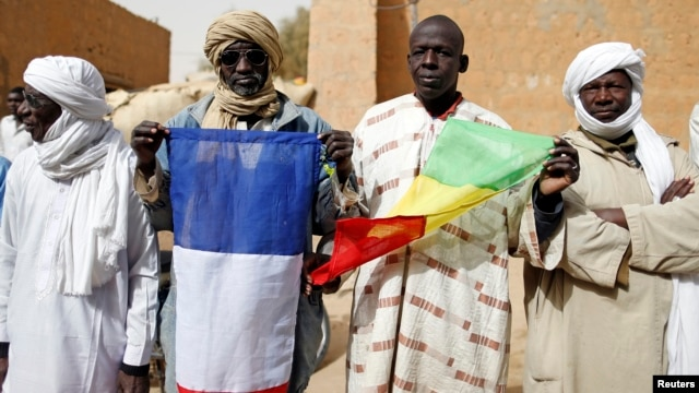 People hold Malian and French flags during the reopening ceremony of Mahamane Fondogoumo elementary school in the town center of Timbuktu February 1, 2013. REUTERS/Benoit Tessier (MALI - Tags: POLITICS SOCIETY EDUCATION) - RTR3D7ZT