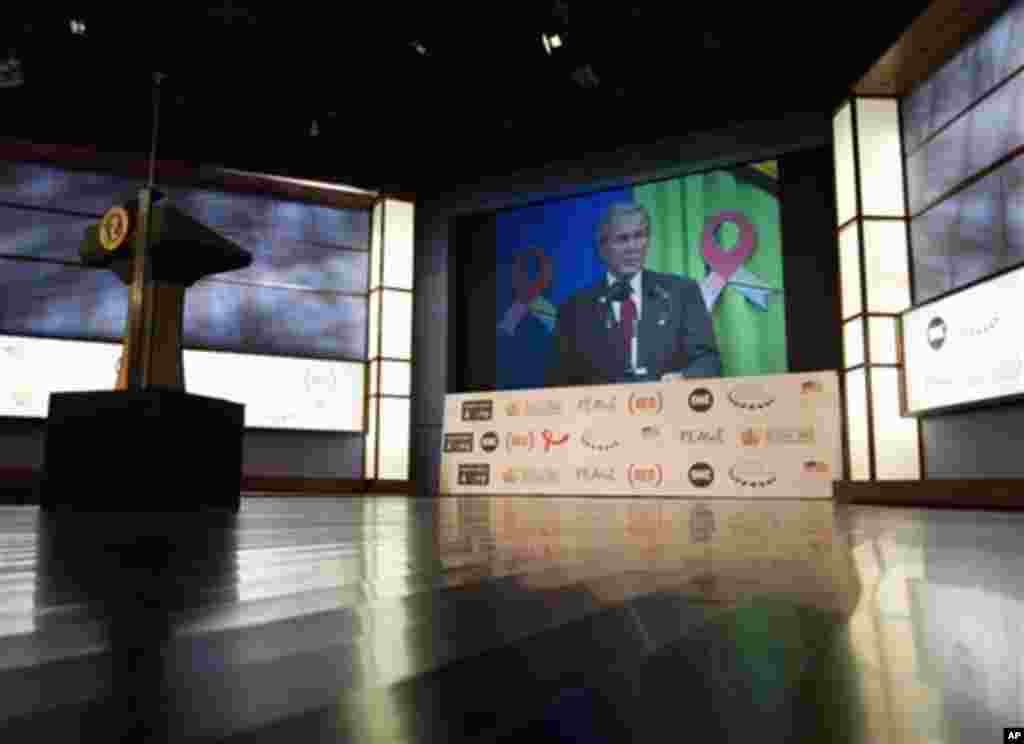 Former President George W. Bush is seen an a large video screen as he speaks to the audience via satellite from Tanzania during a World AIDS Day event at George Washington University in Washington, Thursday, Dec. 1, 2011. (AP Photo/Carolyn Kaster)