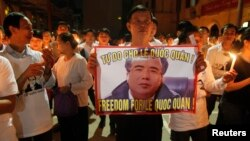 A man holds a poster with the image of lawyer Le Quoc Quan during a mass calling for Quan to be freed at Thai Ha church in Hanoi September 29, 2013. Participants at the mass prayer also called for justice for Quan, a political dissident and pro-democracy