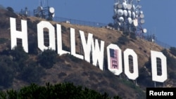 FILE - This 2001 photo shows the famed Hollywood sign in the Hollywood Hills with an American flag positioned over the letter O.