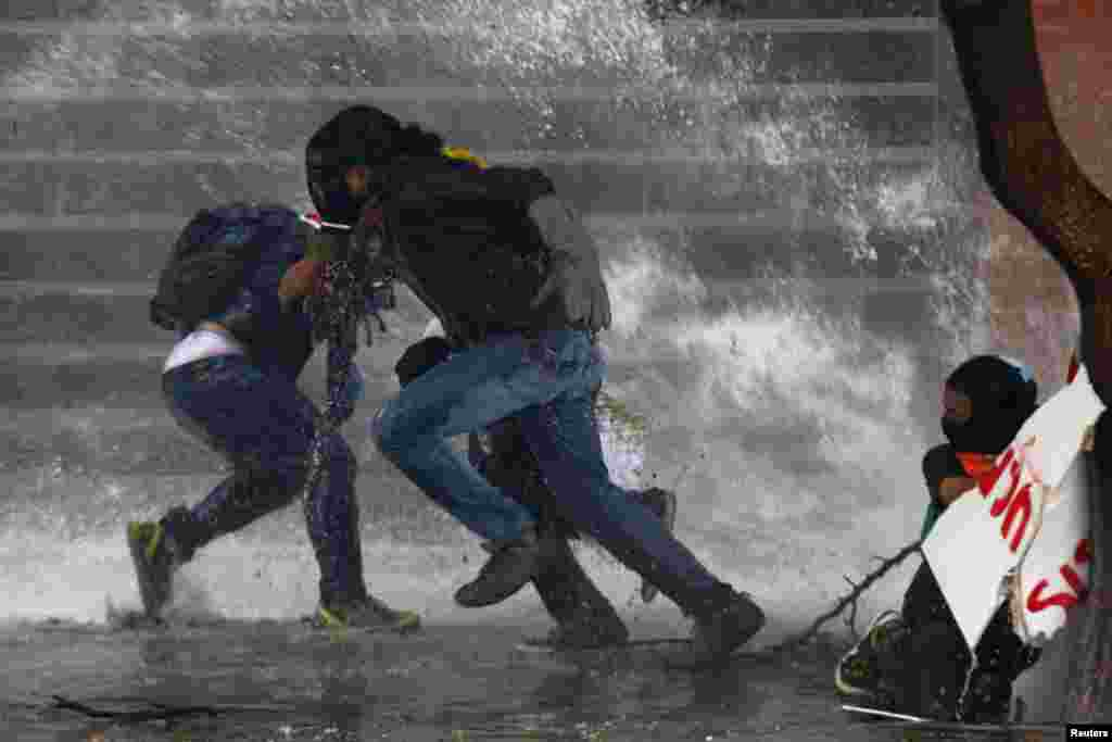 Anti-government protesters run from police water cannon in Caracas, Mar. 20, 2014. Venezuelan intelligence agents arrested one opposition mayor accused of stoking violent protests, while another was jailed for 10 months in the latest moves against rivals of President Nicolas Maduro.