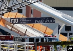 A sign above the rubble of a new pedestrian bridge is shown after the bridge collapsed onto a highway at Florida International University in Miami on March 15, 2018.