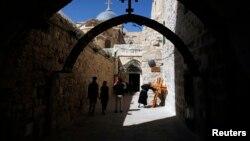 Một linh mục hôn chiếc Thánh giá gần nhà thờ Mộ thánh