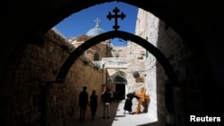 A priest kisses a cross near the Church of the Holy Sepulchre on Good Friday during Holy Week in Jerusalem's Old City, Mar. 29, 2013.