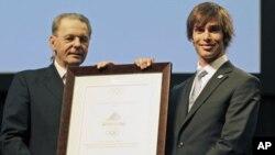 IOC ທ່ານ Jacques Rogge ປະທານກໍາມະການກີລາໂອລິມປິກ ສາກົນມອບ plaque ໃຫ້ທ້າວ Kevin Rolland ທີ່ເມືອງ Durban. ວັນທີ 6 ກໍລະກົດ, 2011