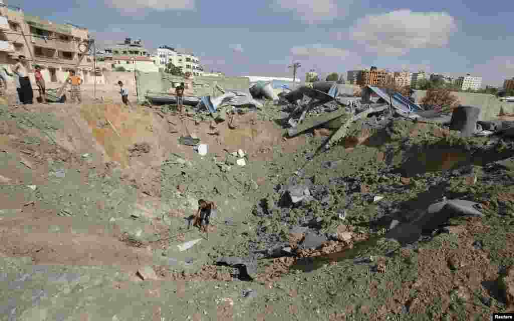 A Palestinian inspects a crater police said was caused by an Israeli air strike in Gaza City, July 3, 2014.