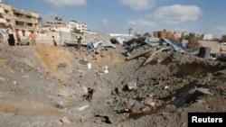 2014年7月3日巴勒斯坦人员检查据称是以色列空袭加沙城造成的弹坑