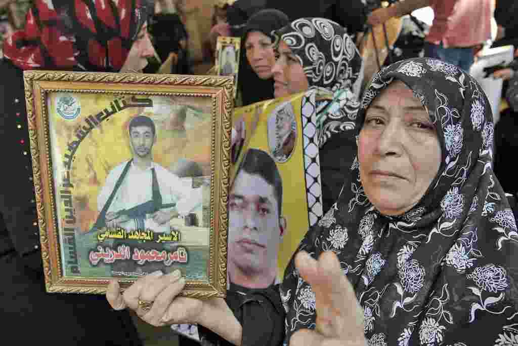 """Una mujer palestina muestra hace la señal de la """"V"""" de victoria y una foto de un familiar encarcelado en Israel, durante una concentración en las oficinas de la Cruz Roja en Gaza para celebrar la liberación de los palestinos."""