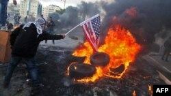 Demonstran Palestina membakar bendera AS dalam aksi protes terhadap keputusan Presiden Donald Trump untuk mengakui Yerusalem sebagai ibu kota Israel, di Beit El, Tepi Barat Kamis (7/12).