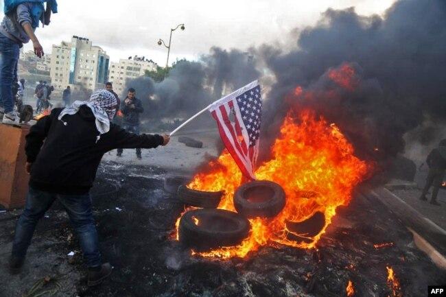 Un manifestante palestino incendia una bandera de EE.UU. en enfrentamientos con tropas israelíes por la decisión del presidente Donald Trump de reconocer a Jerusalén como capital de Israel. La protesta ocurrió cerca del asentamiento judío de Beit El, cercano a Cisjordania. Dic. 7, 2017.