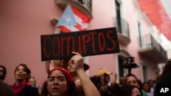 """Una joven sostiene un letrero que dice en español """"Corrupto"""" mientras protestaba frente a la mansión ejecutiva conocida como La Fortaleza, en el Viejo San Juan, exigiendo la renuncia del gobernador Wanda Vázquez después del descubrimiento de un viejo alma"""