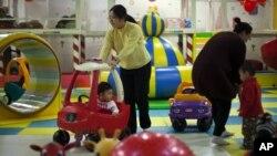 Para ibu dan anak-anak mereka di arena permainan dalam mal di Beijing. (Foto: Dok)