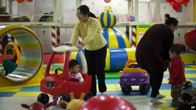 Parents play with their children at a kid's play area in a shopping mall in Beijing. Authors of a new study say the one-child policy has significant ramifications for Chinese society, January 10, 2013.