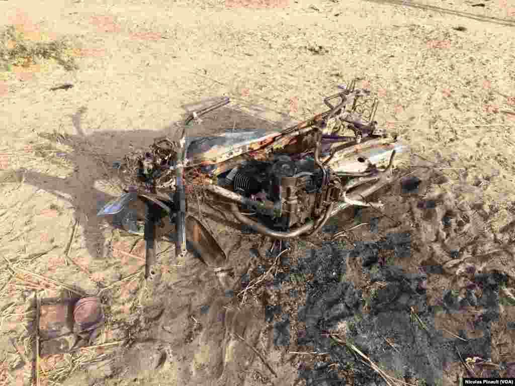 La carcasse calcinée d'une moto appartenant à un assaillant de Boko Haram, dans le village nigérien de Zenam Kelouri, le 29 février 2016. (VOA/Nicolas Pinault)