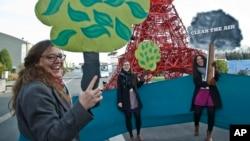 """非政府环保组织的代表在巴黎召开的联合国气候会议的会场旁高喊""""清洁空气,种一棵树""""的环保口号。 (2015年12月5日)"""