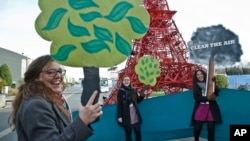 "NGO representatives shout ""clean the air, plant a tree,"" near a reproduction of the Eiffel Tower at the U.N. Climate Change Conference in Le Bourget, north of Paris, Dec. 5, 2015."