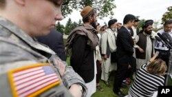 23일 베일리 하사에 대한 선고 후 입장을 발표하는 아프간 주민들의 모습을 미군병사가 지켜보고 있다.